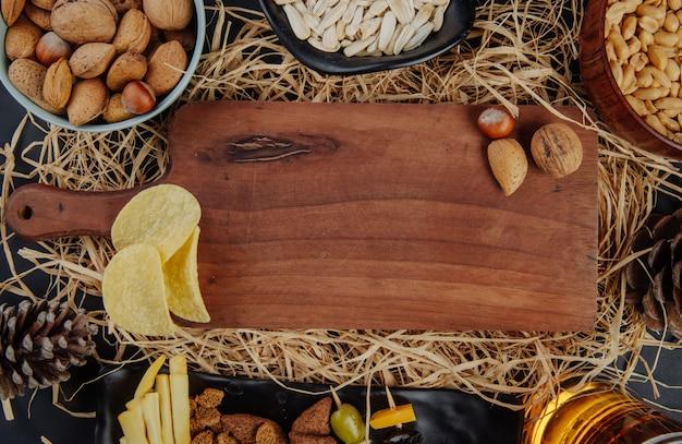 Vista superior de uma placa de madeira com nozes e lanches de cerveja na palha