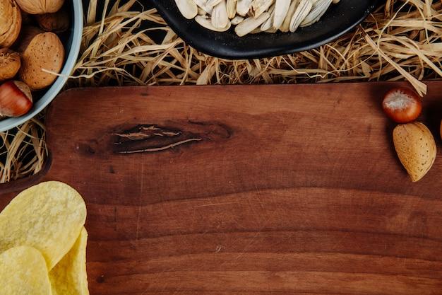 Vista superior de uma placa de madeira e lanches de cerveja na palha