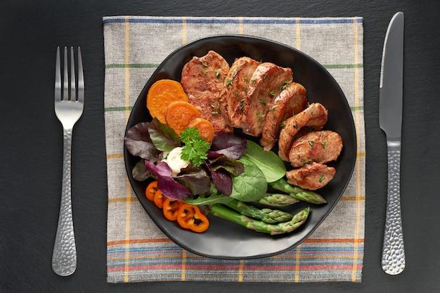 Vista superior de uma placa preta com fatias fritas de carne, batata doce e salada mista em pedra ardósia preta