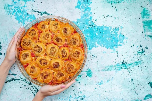 Vista superior de uma refeição de massa cozida com carne picada e molho de tomate dentro de uma bandeja de vidro na mesa brilhante, asse a massa de carne para alimentos