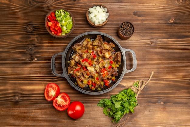 Vista superior de uma refeição de vegetais cozidos com carne e pimentão fresco fatiado em uma mesa de madeira marrom