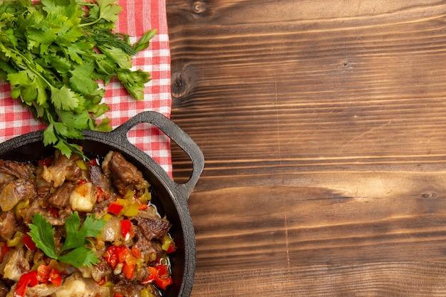 Vista superior de uma refeição de vegetais cozidos, incluindo vegetais e carne dentro de uma mesa de madeira marrom