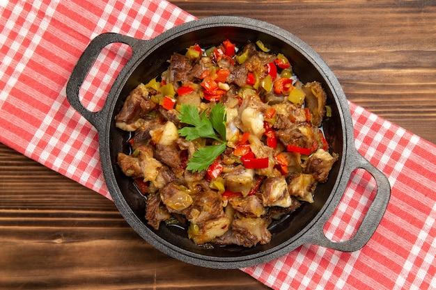Vista superior de uma refeição de vegetais cozidos, incluindo vegetais e carne dentro de uma mesa de madeira