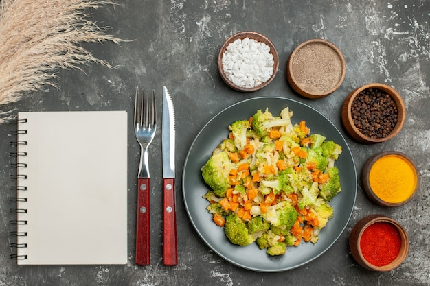 Vista superior de uma refeição saudável com brocoli e cenoura em uma placa preta e especiarias em fundo cinza