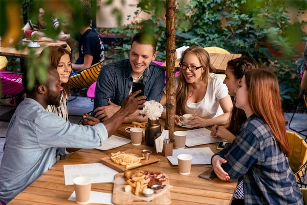 Vista superior de uma reunião amigável de estudantes universitários em seu tempo livre no acolhedor restaurante