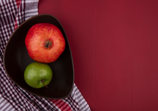Vista superior de uma romã com uma maçã verde em uma tigela com uma toalha quadriculada vermelha em uma superfície vermelha
