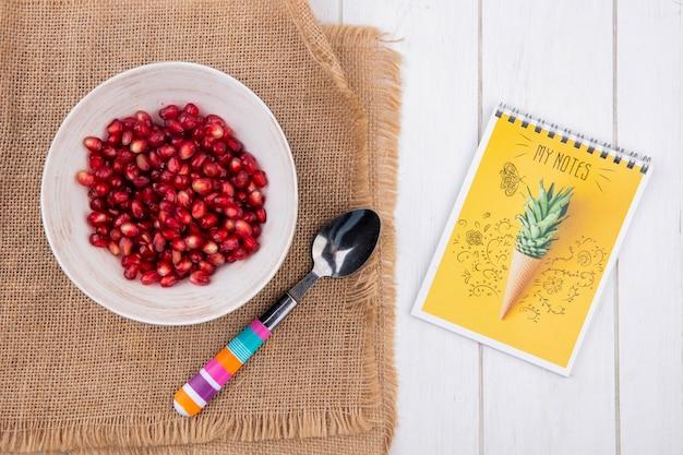 Vista superior de uma romã descascada em um prato com uma colher de chá em um guardanapo bege com um caderno em uma superfície branca