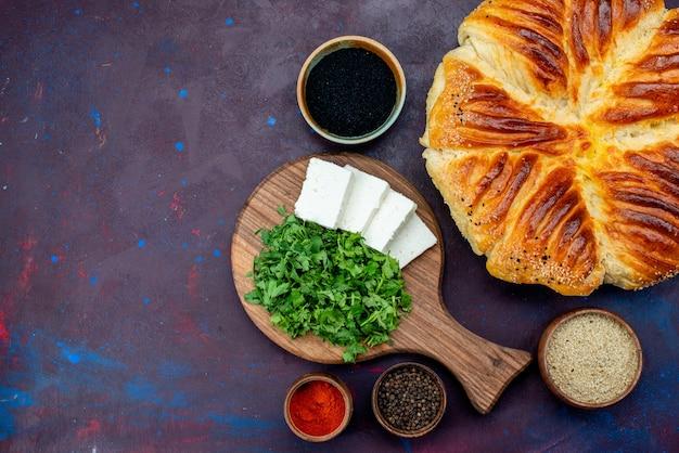 Vista superior de uma saborosa massa assada com verduras e queijo branco na superfície escura