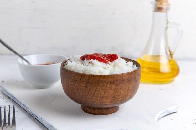 Vista superior de uma saborosa refeição de arroz cozido dentro de uma panela marrom com molho picante e óleo na superfície branca