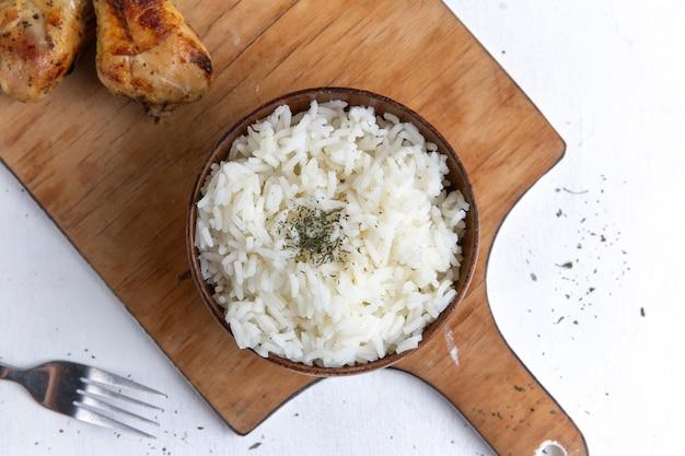 Vista superior de uma saborosa refeição de arroz cozido dentro de uma panela marrom com óleo e frango na superfície branca