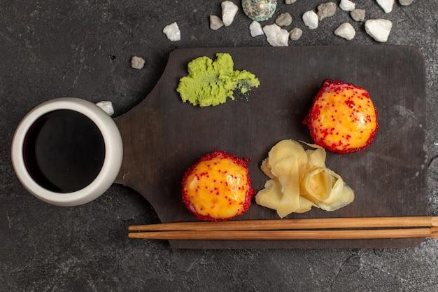 Vista superior de uma saborosa refeição de sushi rola de peixe com peixe e arroz junto com molho na parede cinza
