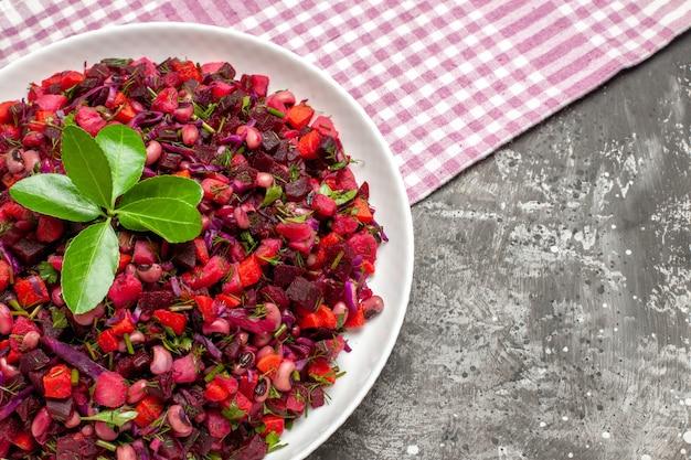 Vista superior de uma saborosa salada de beterraba com vinagrete dentro do prato em fundo escuro