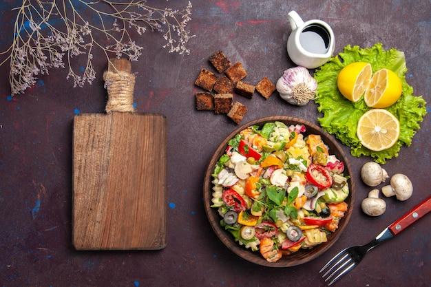 Vista superior de uma saborosa salada de vegetais com rodelas de limão fresco na mesa preta