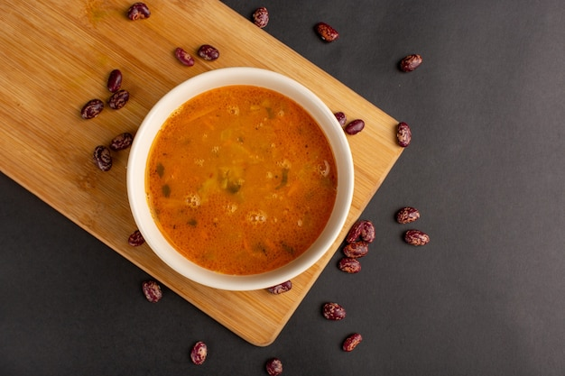 Vista superior de uma saborosa sopa de vegetais dentro do prato junto com feijão cru na superfície escura