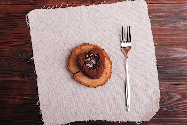 Vista superior de uma sobremesa de chocolate e garfo em uma mesa de madeira