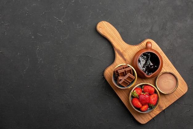 Vista superior de uma sobremesa de longe tigelas de madeira com creme de chocolate e frutas na tábua de cortar na mesa escura