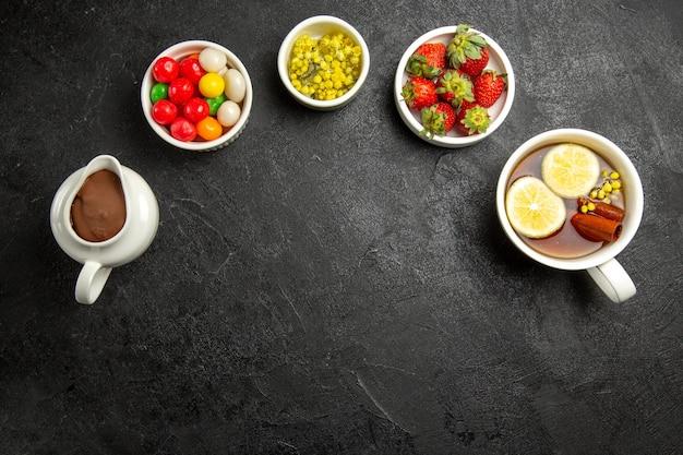 Vista superior de uma sobremesa saborosa de longe quatro tigelas de doces de ervas e morangos com creme de chocolate e uma xícara de chá com paus de canela