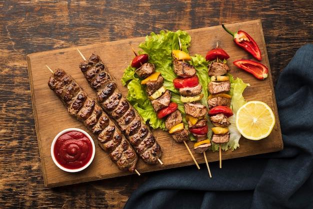 Vista superior de uma tábua de cortar com delicioso kebab e limão