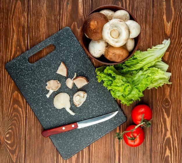 Vista superior de uma tigela com cogumelos frescos e cogumelos fatiados com faca de cozinha em uma placa preta e alface tomate na madeira rústica