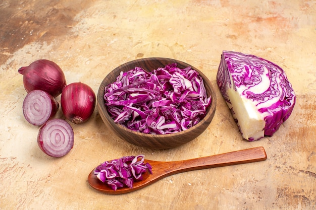 Vista superior de uma tigela de repolho roxo picado e várias cebolas roxas para salada de legumes em um fundo de madeira com espaço de cópia