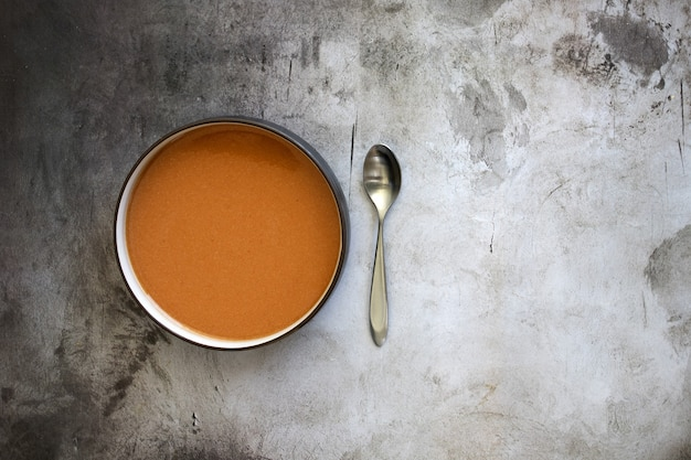Vista superior de uma tigela de sopa com uma colher na mesa sob as luzes