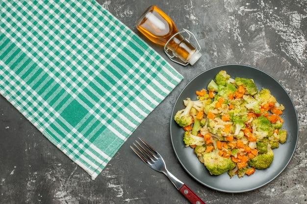 Vista superior de uma toalha verde despojada de salada de vegetais fresca e saudável e uma garrafa de óleo caída