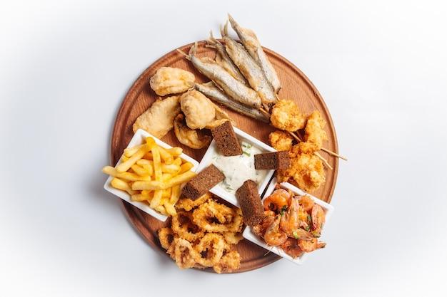 Vista superior de uma travessa isolada de cerveja de frutos do mar fritos com peixes e camarões na placa de madeira