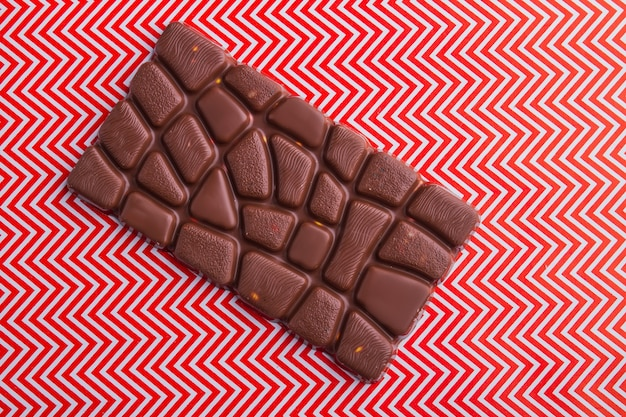 Vista superior de uma única barra de chocolate em fundo vermelho e branco