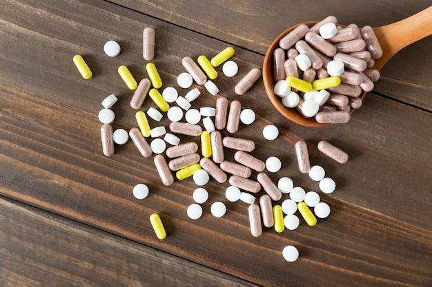 Vista superior de uma variedade de comprimidos, comprimidos e cápsulas de medicamento farmacêutico em uma mesa de madeira escura.