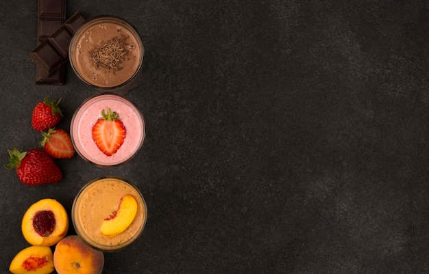 Vista superior de uma variedade de milkshakes com frutas e chocolate com espaço de cópia