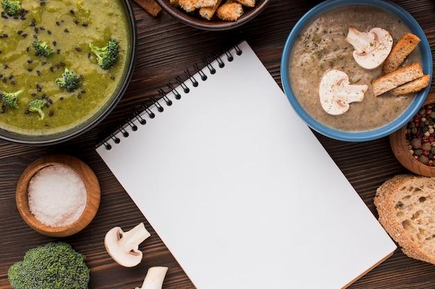 Vista superior de uma variedade de sopas de cogumelos e brócolis de inverno com um caderno