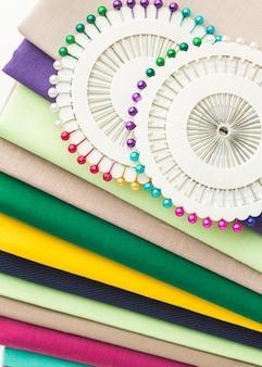 Vista superior de uma variedade de tecidos com agulhas