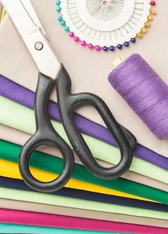 Vista superior de uma variedade de tecidos com tesouras e agulhas