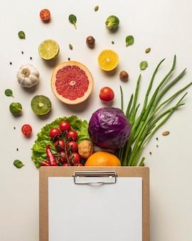 Vista superior de uma variedade de vegetais com prancheta