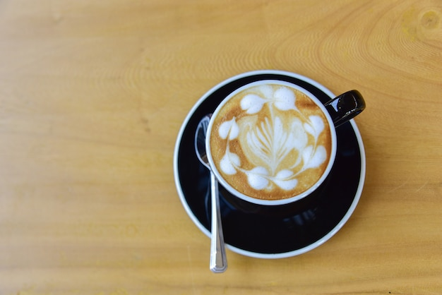 Vista superior de uma xícara de café, arte capuccino, latte art, café com leite quente, cappuccino na mesa de madeira no café