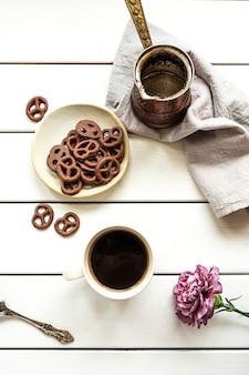 Vista superior de uma xícara de café, cafeteira vazia, pretzels com cobertura de chocolate e uma flor sobre uma superfície de madeira branca. composição do café da manhã ou da pausa para o café.