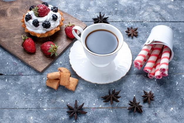 Vista superior de uma xícara de café com biscoitos de morangos vermelhos e biscoitos de palito rosa no chão brilhante.