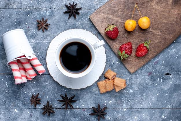Vista superior de uma xícara de café com biscoitos de morangos vermelhos frescos e doces de palito rosa na mesa brilhante, biscoito doce café biscoito