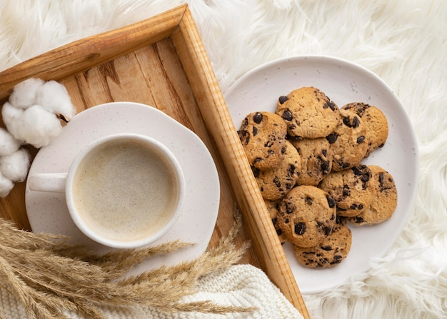 Vista superior de uma xícara de café com biscoitos e flores de algodão