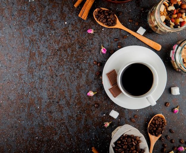 Vista superior de uma xícara de café com chocolate e uma colher de pau com grãos de café sobre fundo preto
