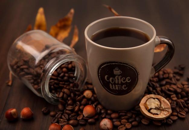 Vista superior de uma xícara de café com grãos de café caindo de uma jarra de vidro em uma superfície de madeira