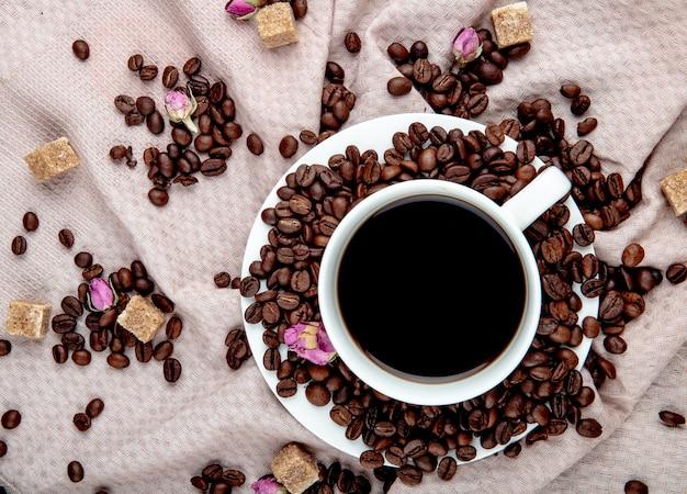 Vista superior de uma xícara de café com grãos de café, cubos de açúcar mascavo e botões de rosa chá