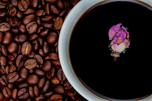 Vista superior de uma xícara de café com grãos de café e chá de rosa em botão