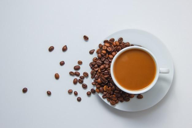 Vista superior de uma xícara de café com grãos de café em pires no fundo branco