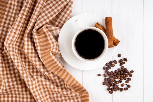 Vista superior de uma xícara de café com paus de canela e grãos de café espalhados em fundo branco de madeira