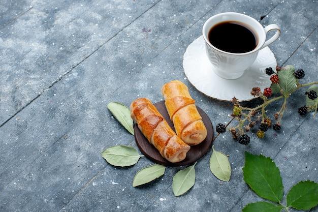 Vista superior de uma xícara de café com pulseiras deliciosas em madeira cinza, bolo de confeitaria doce