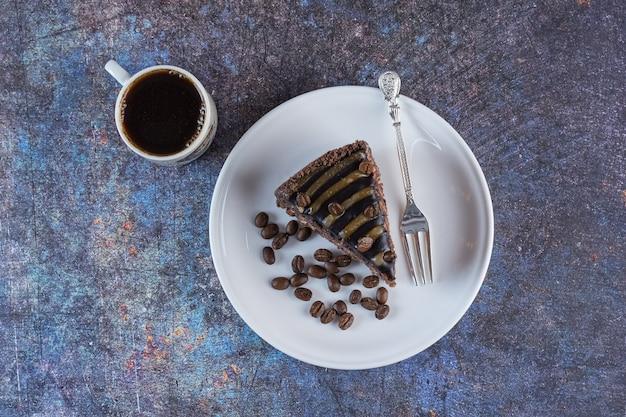 Vista superior de uma xícara de café com uma fatia de bolo de chocolate