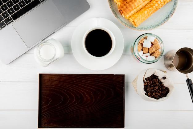 Vista superior de uma xícara de café com wafer rola grãos de café em um laptop de saco e uma placa de madeira no fundo branco