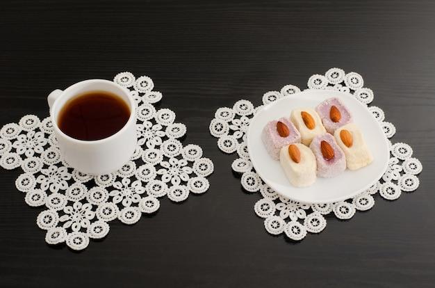 Vista superior de uma xícara de café e delícia turca colorida com amêndoas na mesa preta de guardanapos de renda