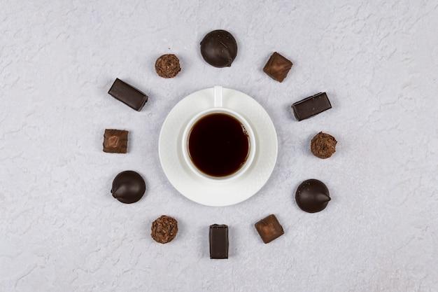 Vista superior de uma xícara de café e doces de chocolate em fundo cinza. postura plana. conceitos de hora da manhã e despertador